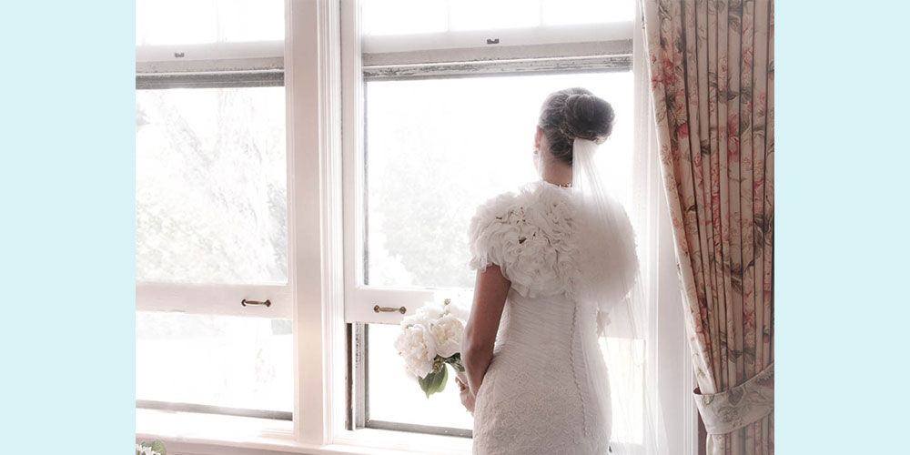 A bride looks out the window as she waits for her ceremony to begin.