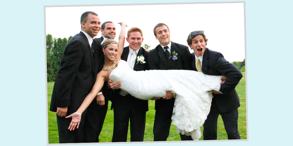 A groom and his groomsmen pick up a bride and hold her sideways across their arms.