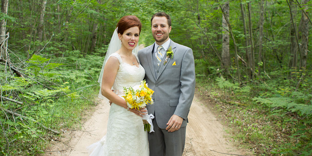 A bride and groom stand on a dirt road in the woods